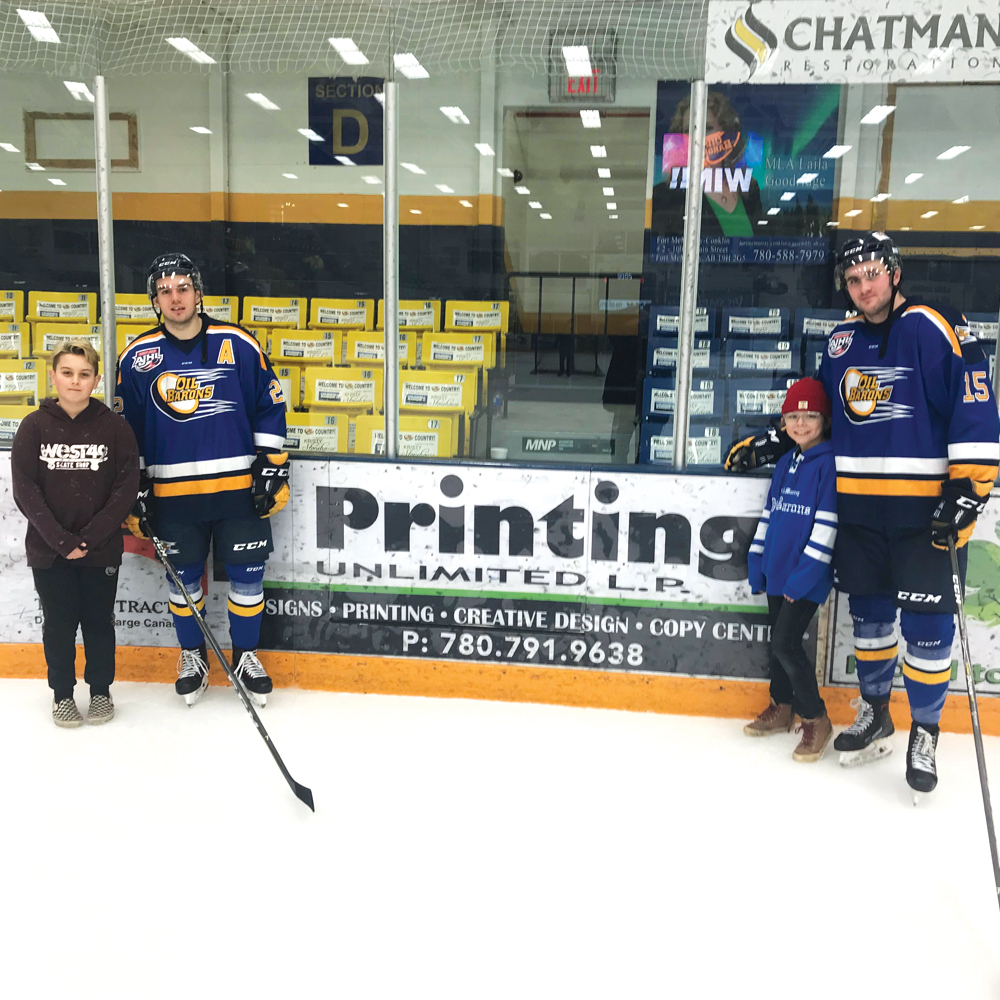 Two small boys and two hockey players on the ice stand around a Printing Unlimited banner on the side board of the rink