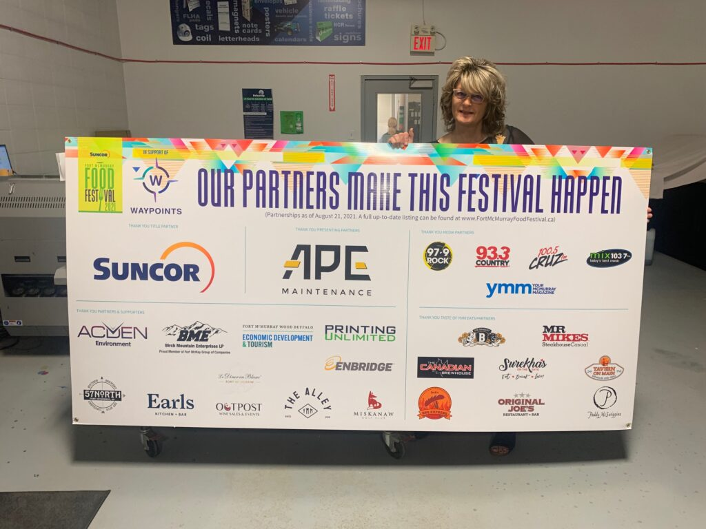 A Printing Unlimited staff member holding up a large banner with a list of sponsors, including Printing Unlimited, for the Fort McMurray Food Festival