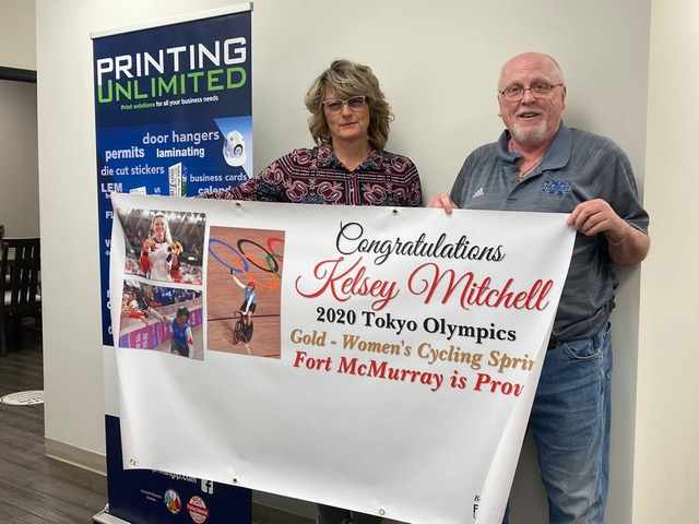 Natalie Kemeny, Printing Unlimited General Manager, and journalist Curtis J. Phillips, holding the congratulations banner for Kelsey Mitchell