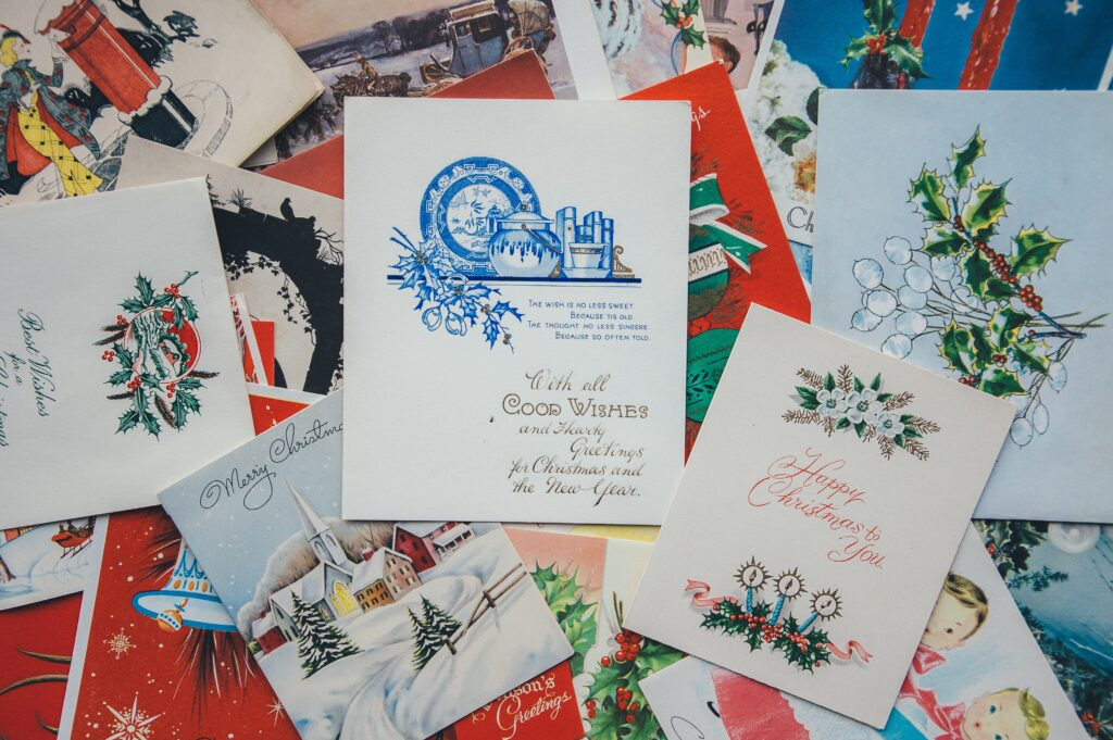 A pile of custom Christmas cards with an assortment of colours, images, text and styles, from unsplash.