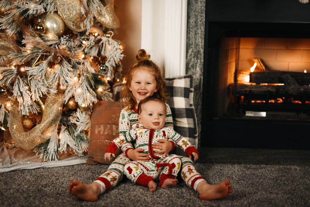 A family photo for a custom christmas card, with two young children, a young girl holding her baby sibling, in matching pajamas siting in front of their Christmas tree by the fireplace.