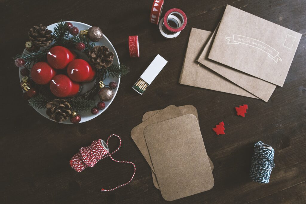 Custom christmas cards in the process of being made on a dark wooden table, with red candles, evergreen leaf decorations, red and white string, red ribbon and thick, brown card stock paper, from unsplash