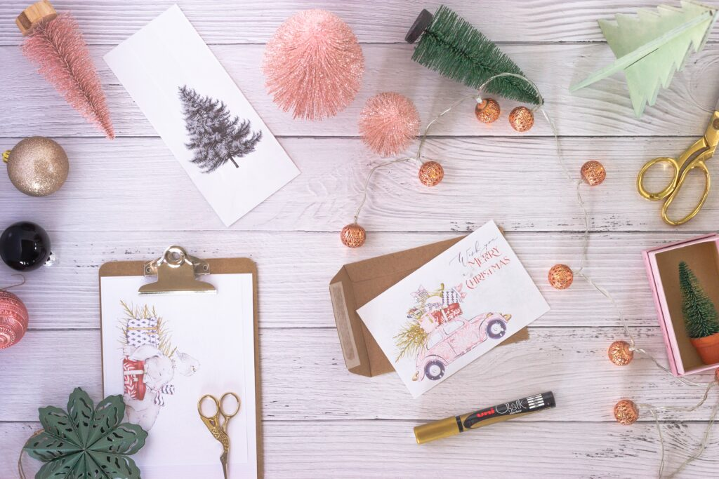 White card stock being made into custom Christmas cards, with illustrations of a Christmas tree and other Christmas decorations on them, along with Christmas decorations around the cards on a wooden white-panelled table, from Unsplash.